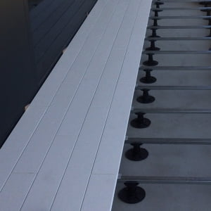Galvanized bars, thermoplastic pedestals with variable height and fixing clips.
